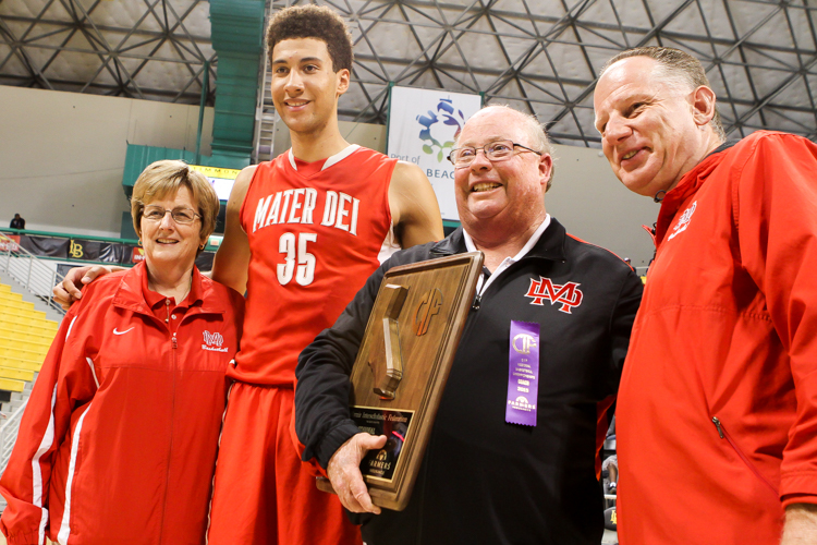 Mater Dei Head Coach Gary Mcknight with the Regional Trophy flaked by #35 MJ Cage and Staff