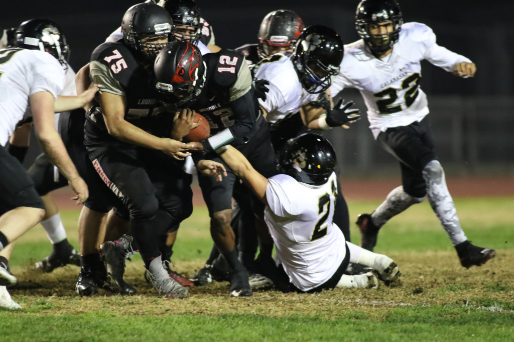 Nov 20 : Lawndale Cardinals quarterback Chris Murray (C) (12) fighting for extra yards  in quarterfinals of CIFSS Playoffs with Calabasas vs. Lawndale at Lawndale High School in Lawndale, Ca (Photo by Jevone Moore/Full Image 360)