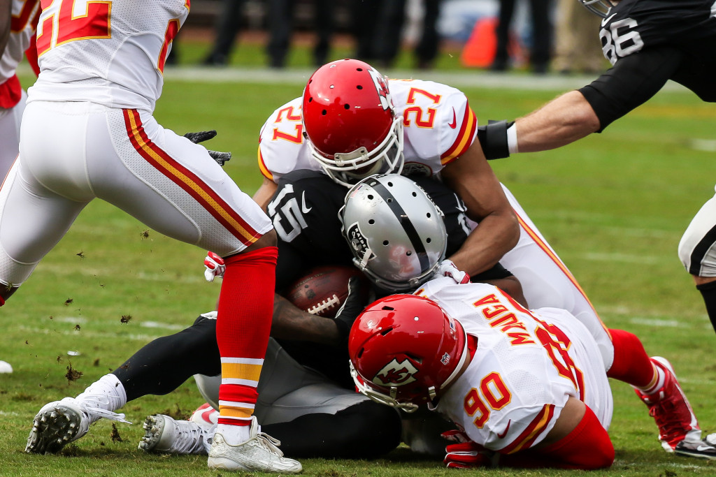 Dec 6: NFL Kansas City Chiefs inside linebacker Josh Mauga (90) & defensive back Tyvon Branch (27) smashing wide receiver Michael Crabtree (15) in the First half game action Kansas City Cheifs vs Oakland Raiders at Oakland Coliseum in Oakland Ca. (Photo by Jevone Moore/Full Image 360)