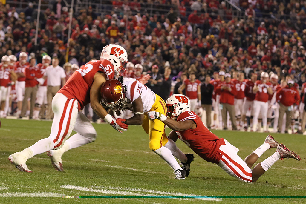 Wisconsin Badgers linebacker T.J. Edwards (53) & cornerback Sojourn Shelton (8) tackle USC Trojans running back Ronald Jones II (25) during the National Funding Holiday Bowl between the USC Trojans vs Wisconsin Badgers on Wednesday Dec 30th, 2015. (Photo by Jevone Moore/fi360 News)
