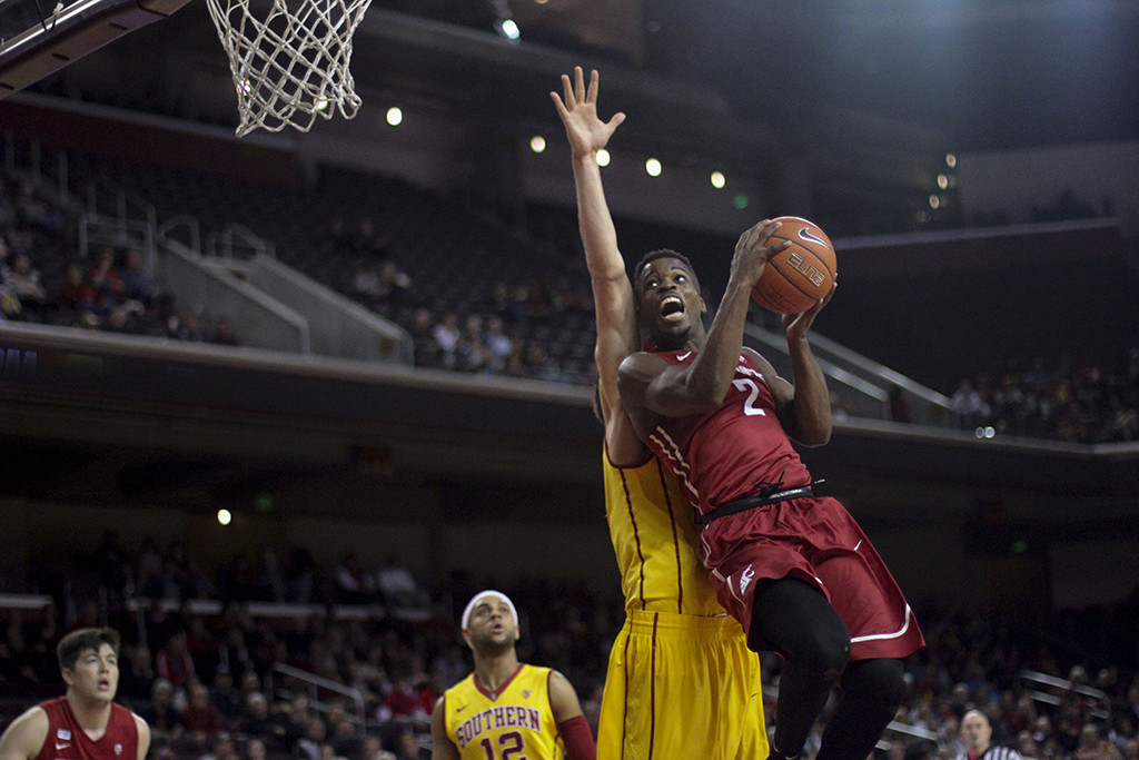Ike Iroegbu trying to get pass USC defender to the hoop during first half of the Washington State vs USC game at the Galen Center in Los Angeles, CA. (Photo by Michael Ewing/fi360 News)