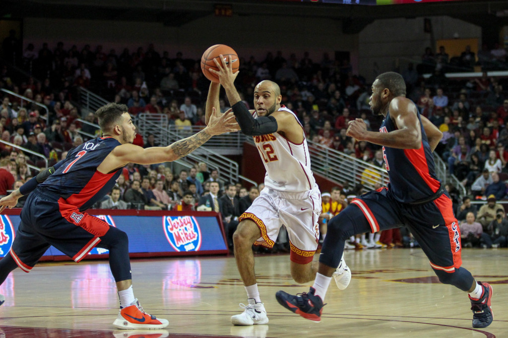 USC Trojans guard Julian Jacobs (12) slices between two Wildcats during the college basketball game between the Arizona Wildcats and the USC Trojans at Galen Center in Los Angeles, CA. (Photo by  Jordon Kelly)